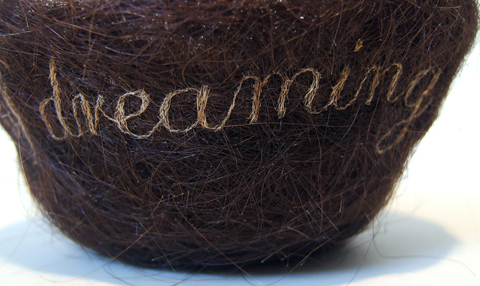 """Kate Kretz - """"Decades of Dreaming of You..."""", 2012, hair embroidery on mother's hair from gestation period, threads from unraveled pillowcase, 3 x 5 x 5"""". Embroidered text reads, """"decades of dreaming of you..."""""""