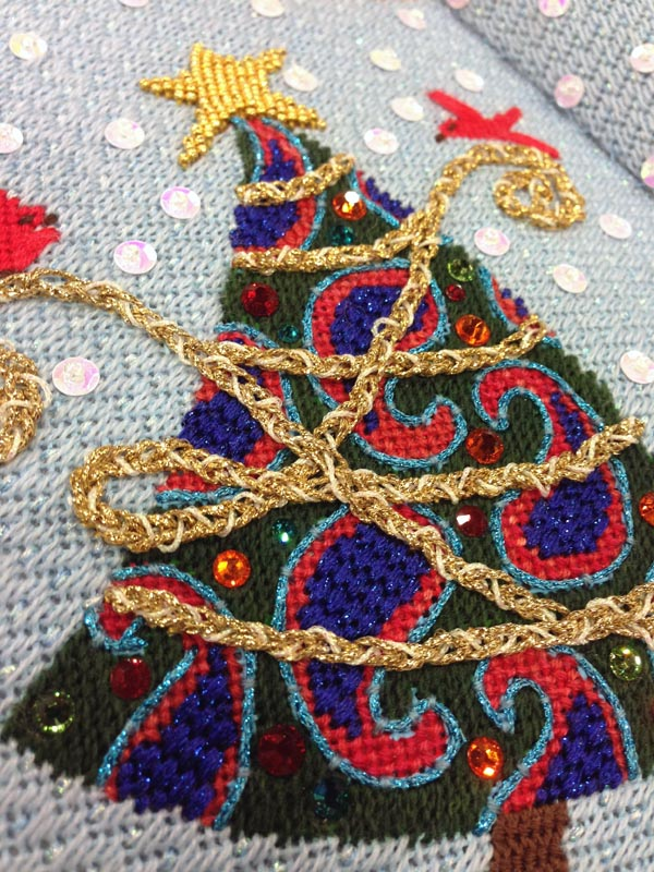 A variety of threads, sequins, beads and stitches bring this painted needlepoint canvas to life.