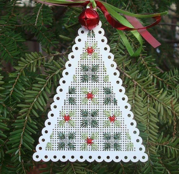 Metallic and reflective thread in sparkling straight stitches on a perforated paper tree shape.