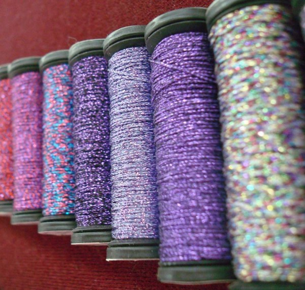 I love this photo, taken at the Kreinik thread factory, because it shows some of the variegated colors they make. It comes from an old thread display, but I believe all but the color on the far right are still produced.