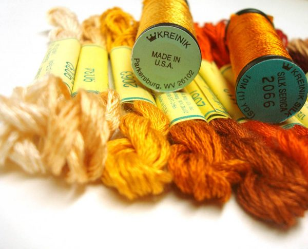 Two types of silk thread are shown here: Kreinik Silk Mori, a spun silk (the skeins) and Kreinik Silk Serica, a filament silk (the spools). You can see the difference in texture and sheen. From http://www.kreinik.com/shops/Silk-Threads/