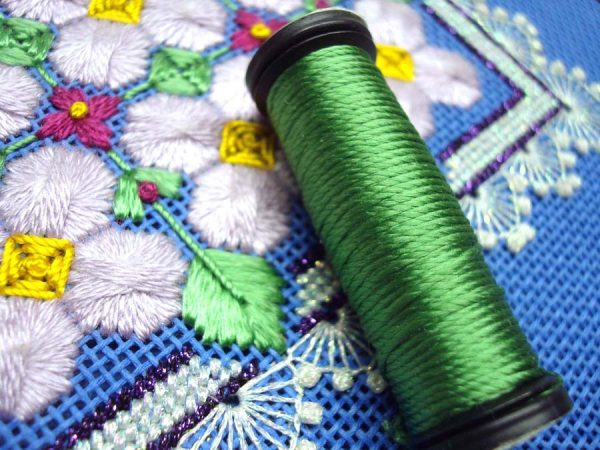 This needlepoint design by Mary Polityka Bush features Kreinik Silk Mori (the purple flowers) and Kreinik Silk Serica (the green leaves). To make the leaves, the Serica is separated, moistened with a slightly damp cosmetic sponge to remove the waves, and laid as a flat silk (for optimum sheen).