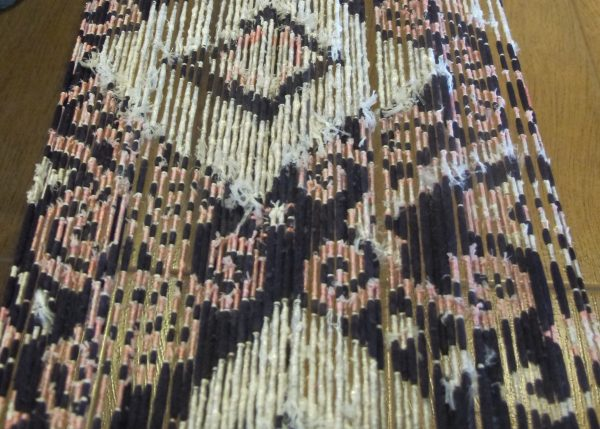 An Ikat in process. The warp threads are bound according to the pattern and is awaiting the next colour dye