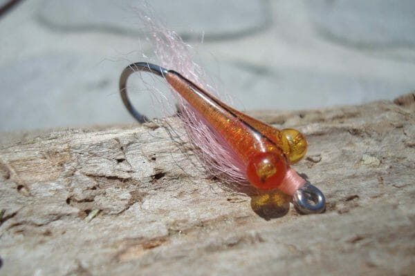This fly fishing lure looks alien to me, but I bet it's irresistible to fish. The body is wrapped with metallic threads, then covered with a clear epoxy, which lets some of the shimmer come through. Creative mix of materials.