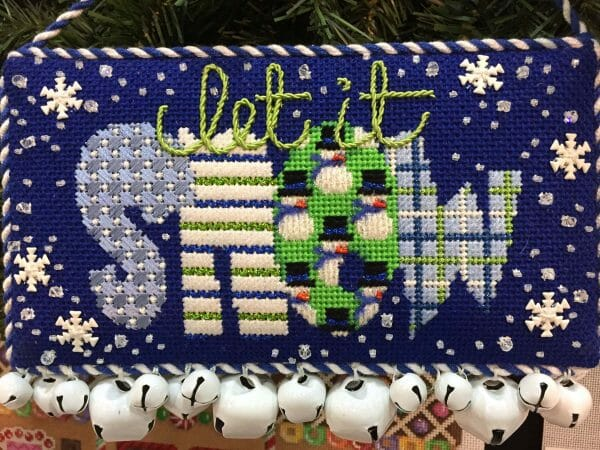Stitching snow can make winter downright enjoyable. Play with metallic threads to create realistic looking snow, have fun with a variety of stitches, and create something beautiful this month. Canvas by Associated Talents needlepoint company.