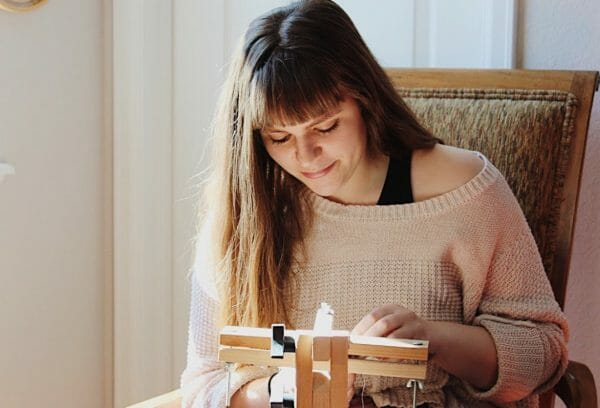 Carly Owens stitching at her frame.