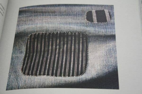 Beauty in mending, patterned pieces are used to cover holes in denim to mend and patch.