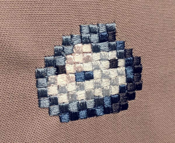 Finished Blue Slime Pixel Art Embroidery design by Erich Campbell seen from an angle