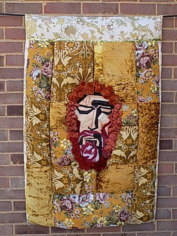 Christine Cunningham - Jesus 2 - The flat applique face of Jesus is inset by padded panels created from vintage fabrics from my childhood.