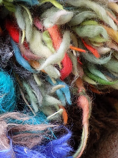 Use wool pompoms to create depth and structure within a textile